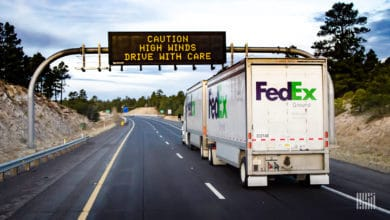 "FedEx truck heading down highway with ""Caution: High Winds"" digital sign ahead."