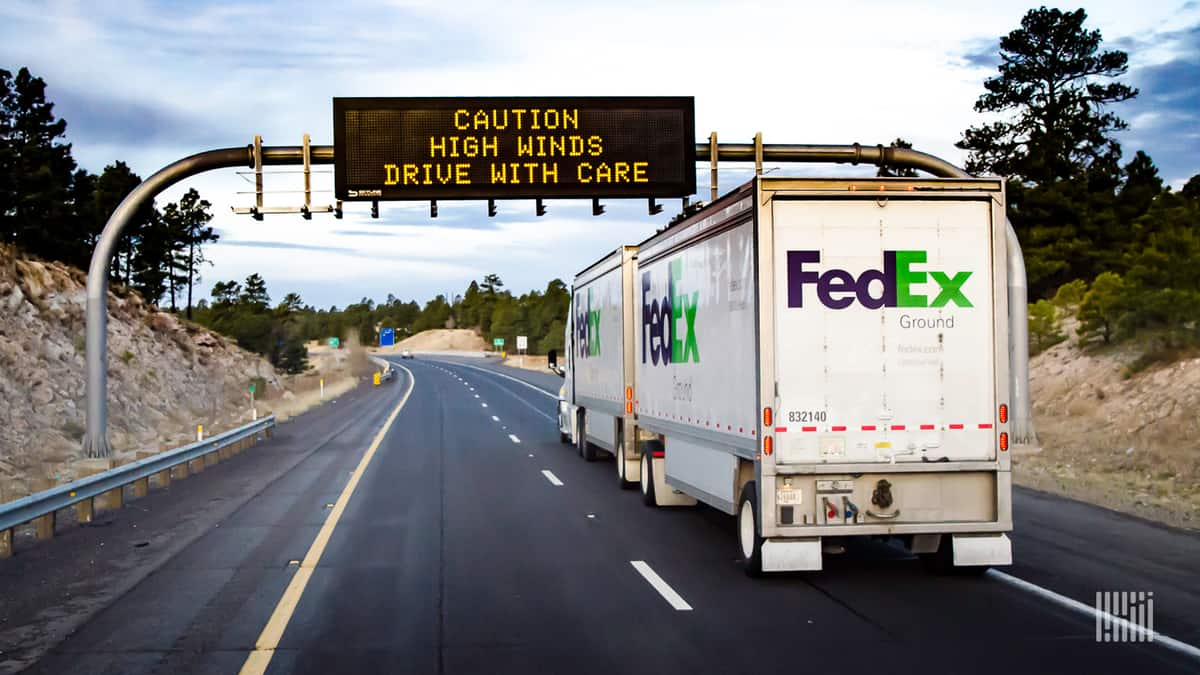 """FedEx truck heading down highway with """"Caution: High Winds"""" digital sign ahead."""