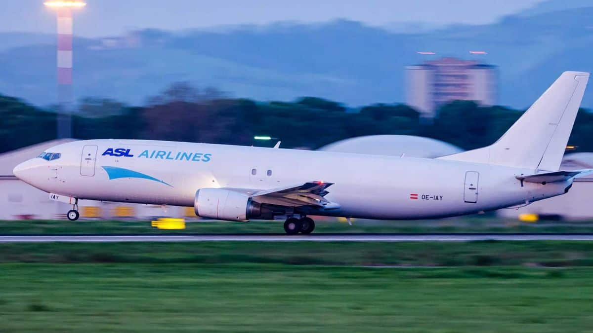 A white cargo jet touches down on runway.