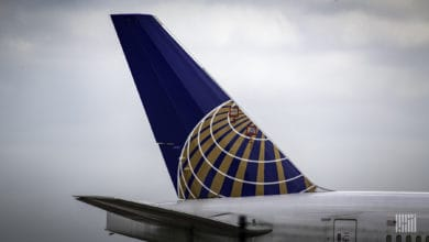 Blue tail fin of a United jet against a gray sky.