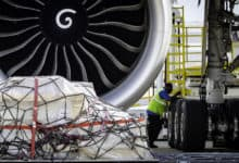 A cargo pallet rests on the ground in front of a big jet engine.