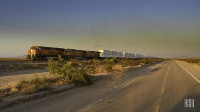 A photograph of a BNSF train hauling intermodal containers across a field.