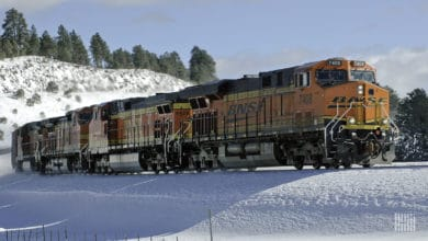 A photograph of a BNSF train traveling through a snowy field.