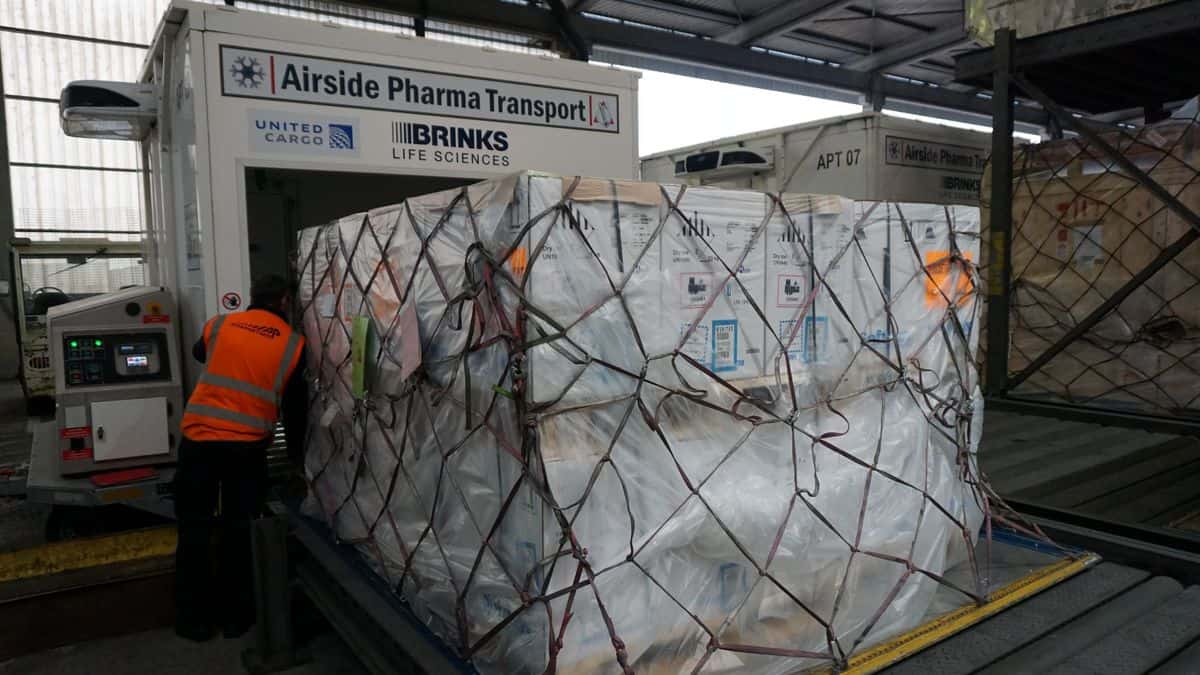 A large pallet of white boxes tied down with netting in an airport terminal.