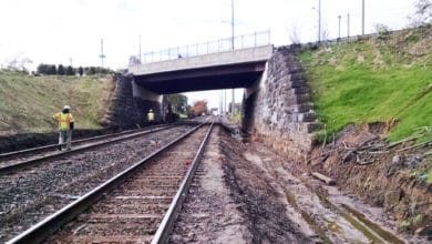 A photograph of train tracks heading under a bridge.