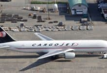 White cargo jet with blue tail sitting in front of cargo hangar. View from above in plane taking off.