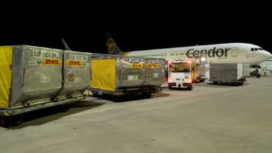 Pallets of air cargo on carts waiting to be loaded into a white plane at night.