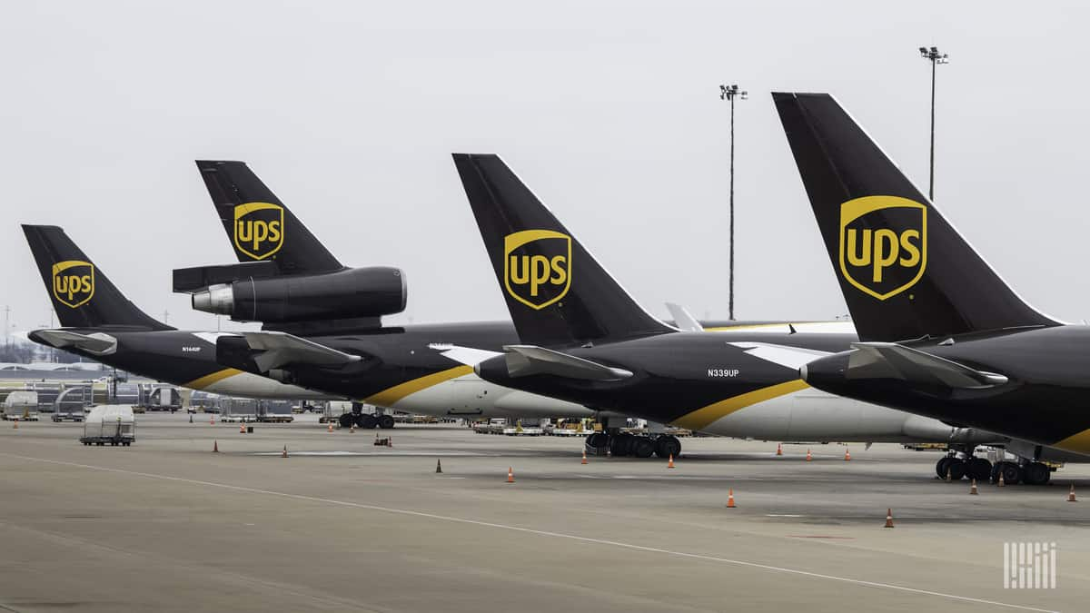 Brown-tails of UPS planes in a row at airport.