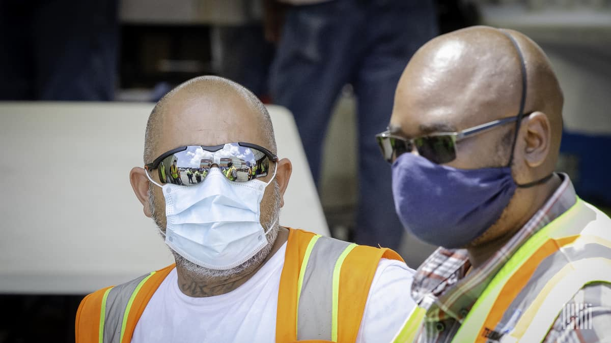 Workers wearing sun glasses and face masks.