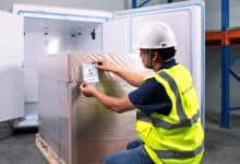 A man with a hard hat and yellow vest kneels to place label on small pallet before putting into refrigerator.