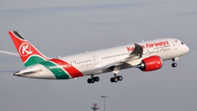 A white jet with red tail on take off with wheels still down. Kenya Airways.