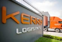 An orange Kerry Logistics truck entering road from Kerry facility next to company sign.