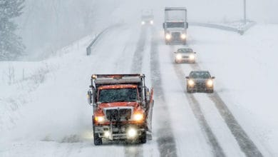 Cars and tractor-trailers behind a plow truck on a snowy Michigan highway.