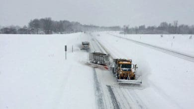 Plow trucks clearing a snowy New York highway.