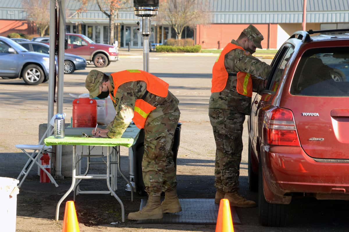 Members of the Oregon Army National Guard prepare to administer COVID-19 vaccines during a mass vaccination clinic in Eugene, Oregon.