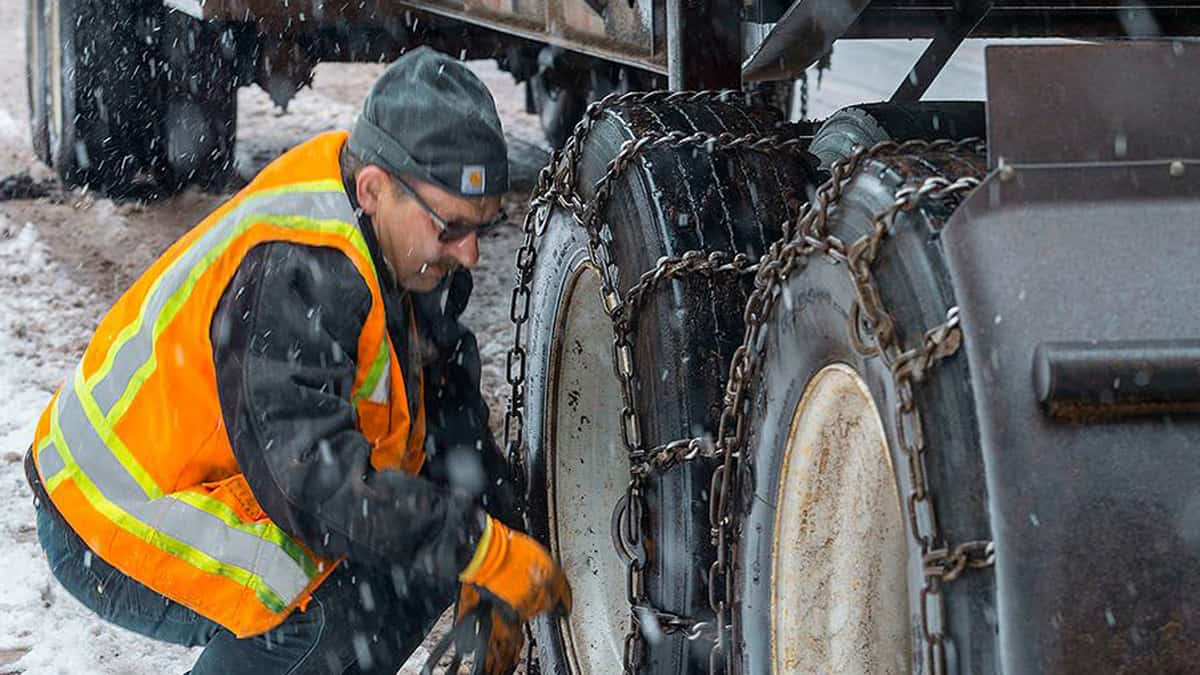 Driver putting chains on his tires as snow falls.