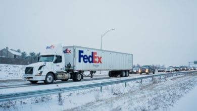 FedEx truck heading down snowy Pennsylvania highway with traffic behind it.