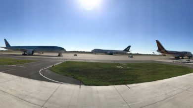 Landscape photo of three planes on tarmac on sunny day