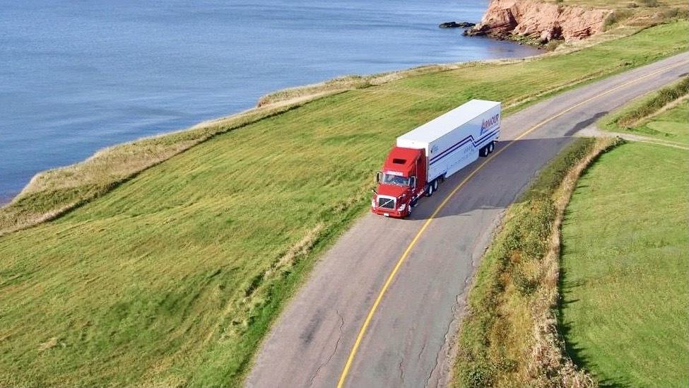 A photograph of a truck driving by a lake.