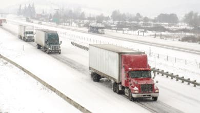 Tractor-trailers heading down snowy highway.