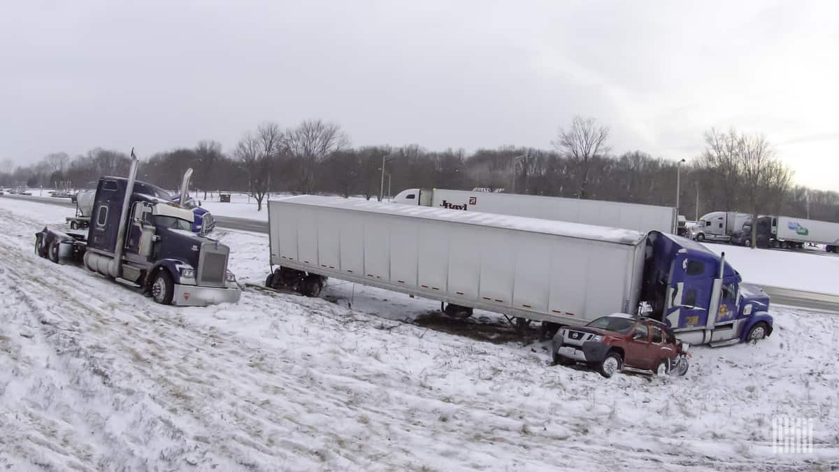 Tractor-trailers and cars stuck on side of snowy highway.