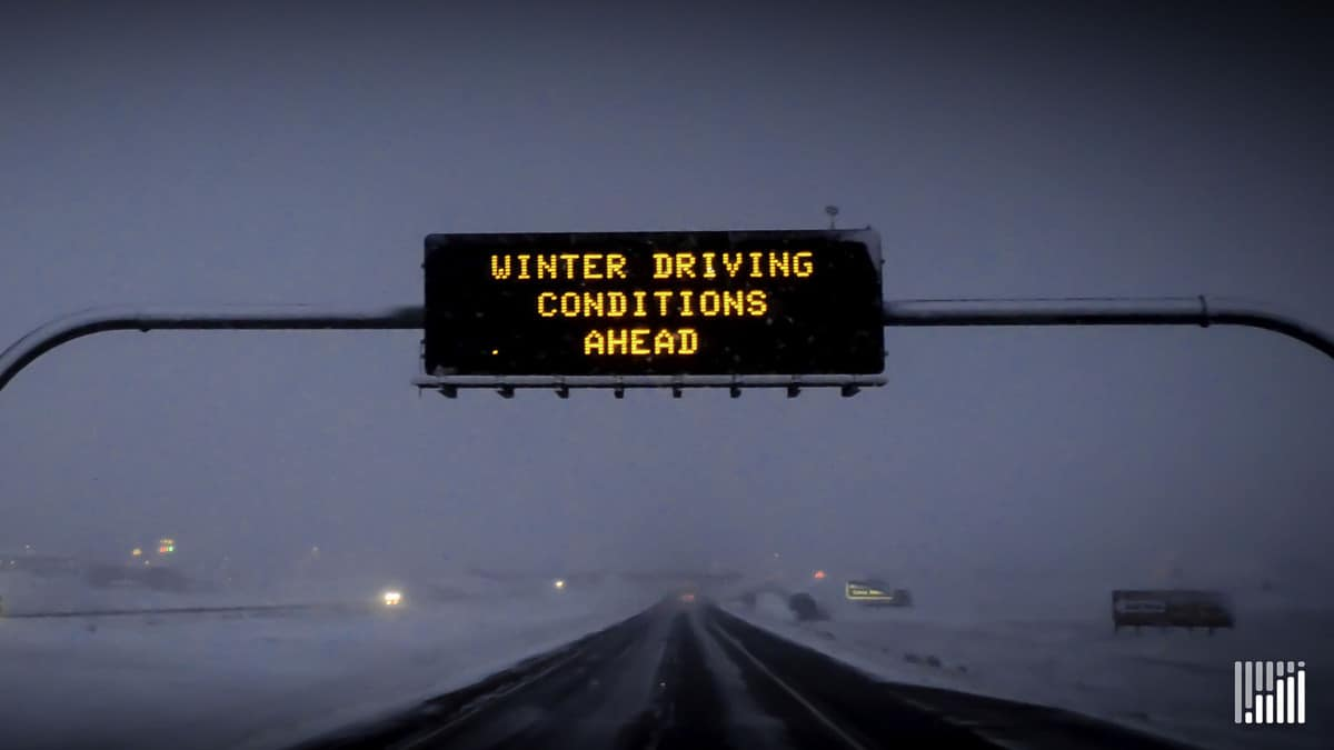 """Winter Driving Conditions Ahead"" digital sign above snowy highway."