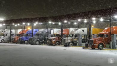 Several tractor-trailers parked at truck stop on a snowy night.