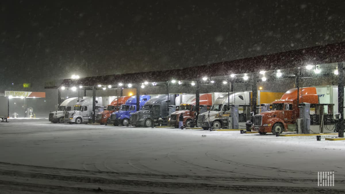 Tractor-trailers parked at a truck stop on a snowy day.