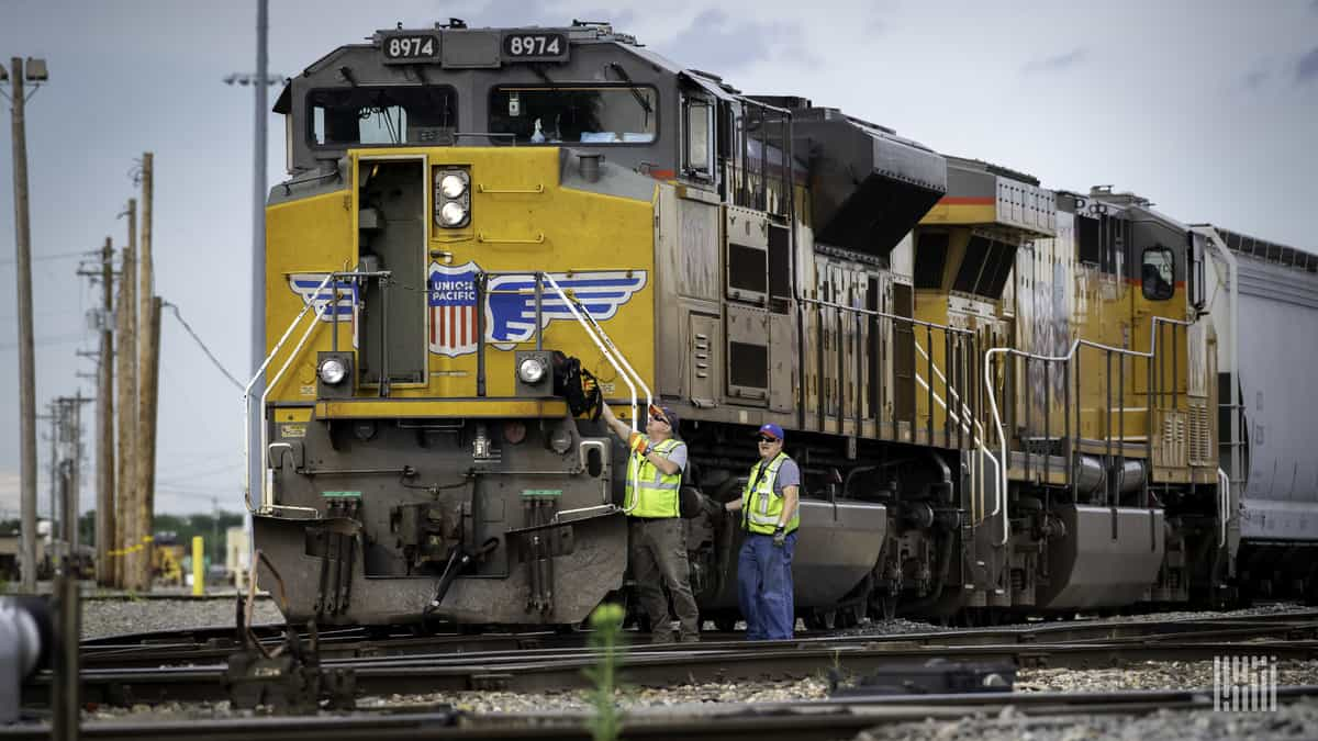 A photograph of two people in front of a Union Pacific locomotive.