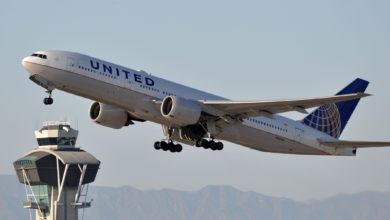 A big United Airlines jet takes off with control tower behind it.
