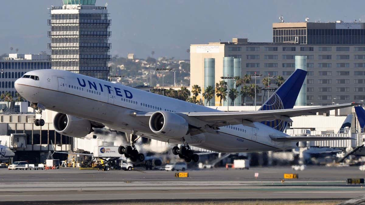 A big United Airlines jet lifts off runway on sunny day at LAX airport.