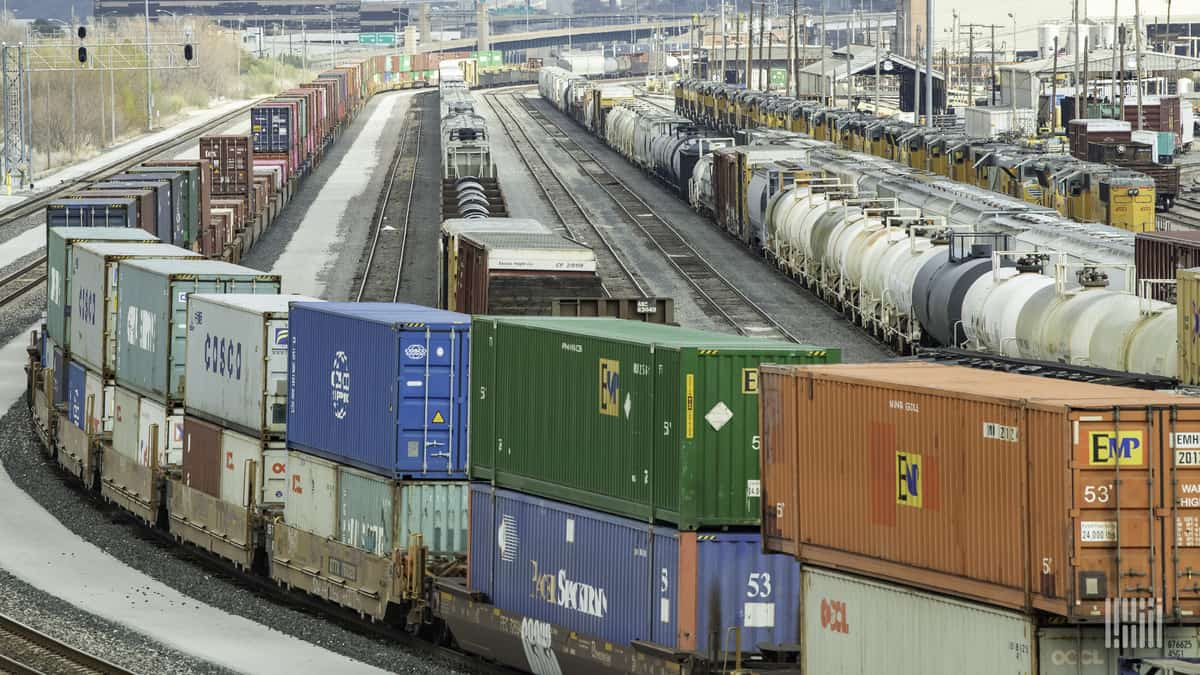 A photograph of intermodal containers and tank cars parked at a rail yard.