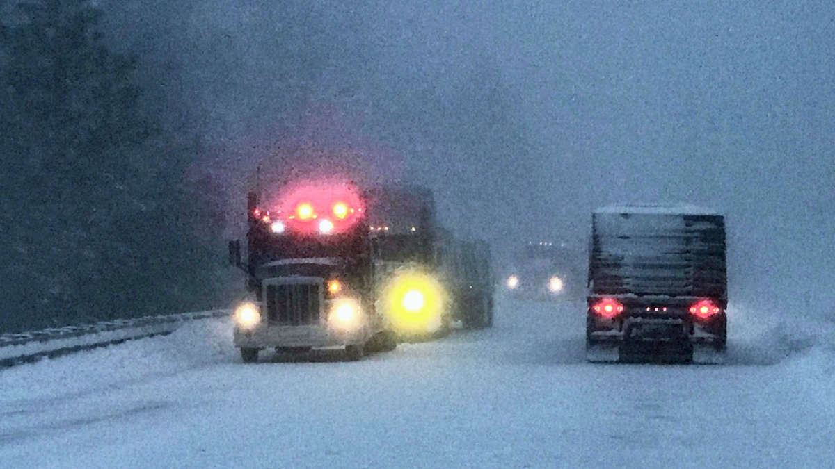 Tractor-trailers heading down a Washington highway on a snowy day.