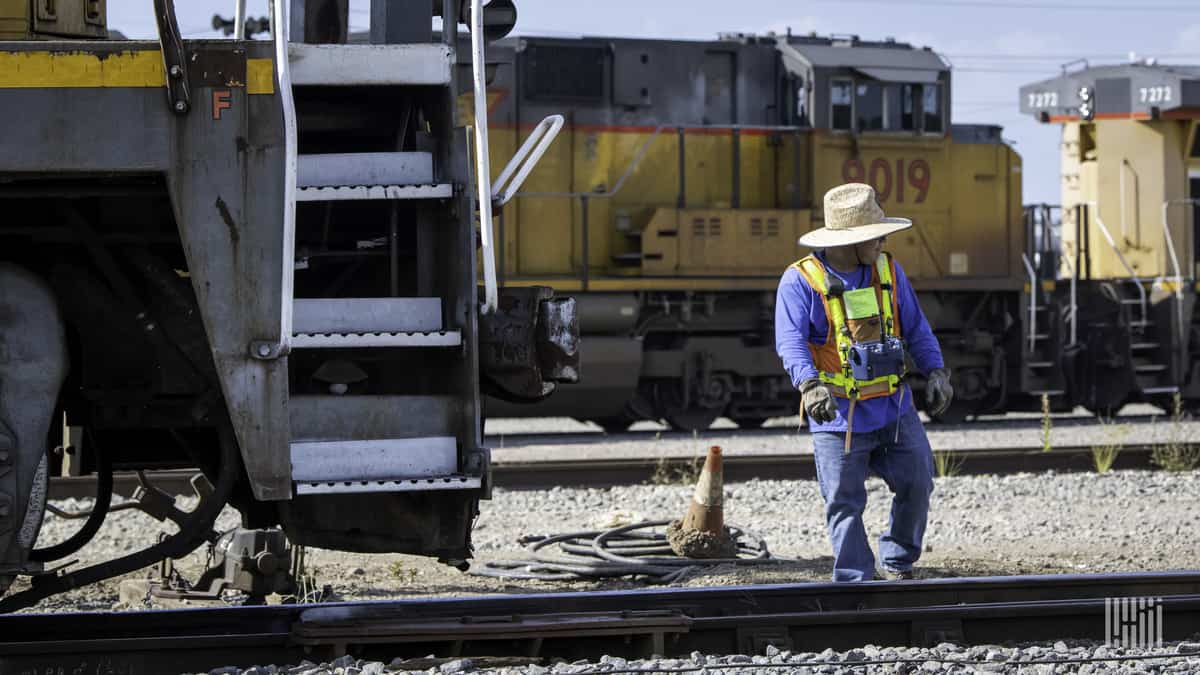A photograph of a man working in a rail yard.