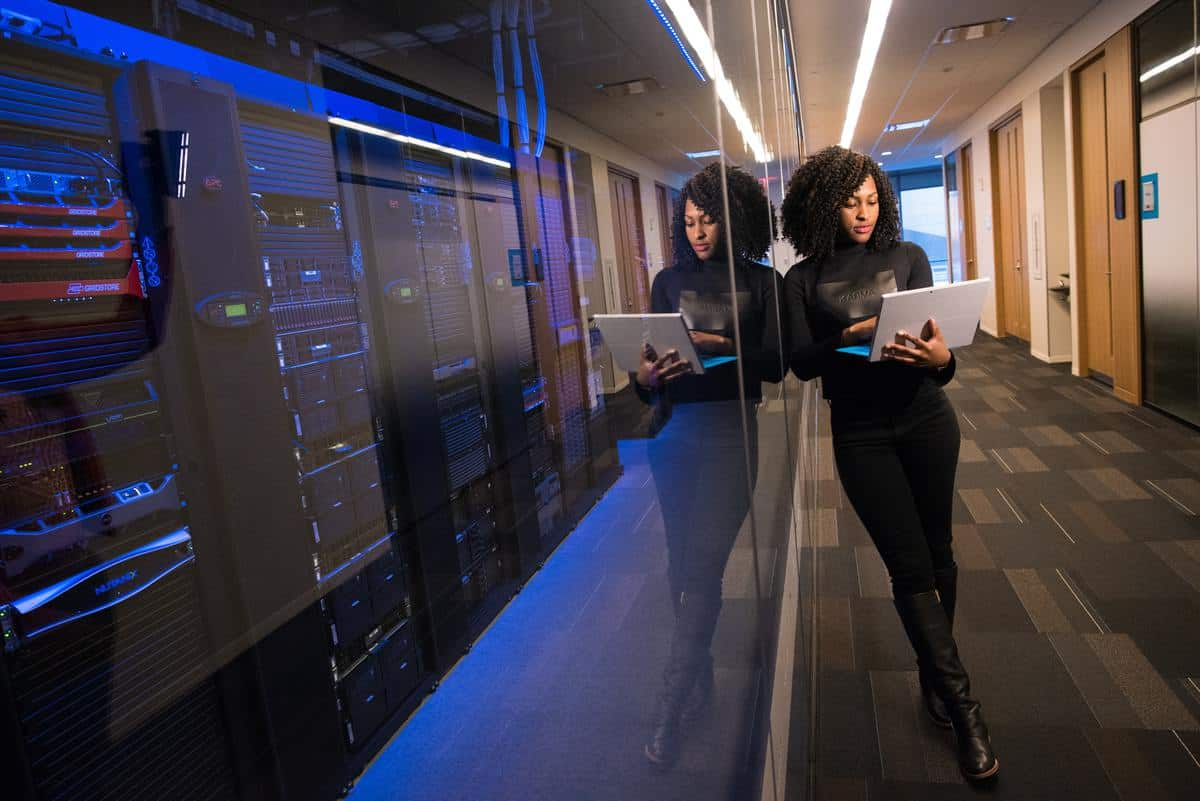 Woman standing outside server room holding laptop