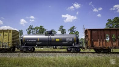 A photograph of a tank car and two railcars parked in a rail yard.