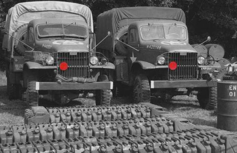Red Ball Express trucks with fuel cans lined up in front of them.  (Photo courtesy of American Battle Monuments Commission)