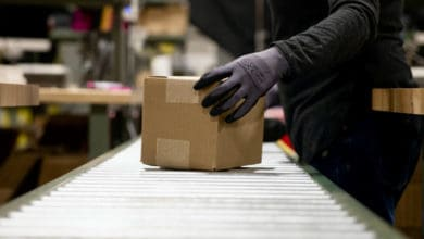 A package is handled by a warehouse worker wearing gloves at a Shopify fulfillment network facility.