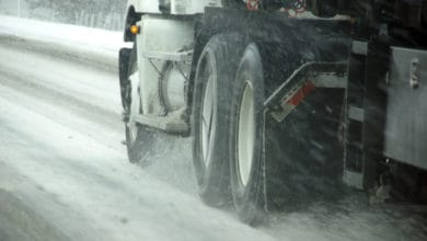 Tractor-trailer heading down slushy/icy road.