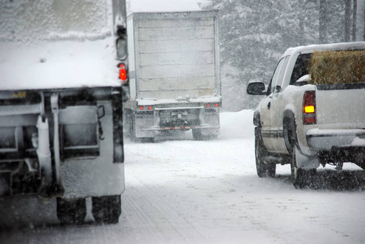 Tractor-trailers heading down a snowy highway.