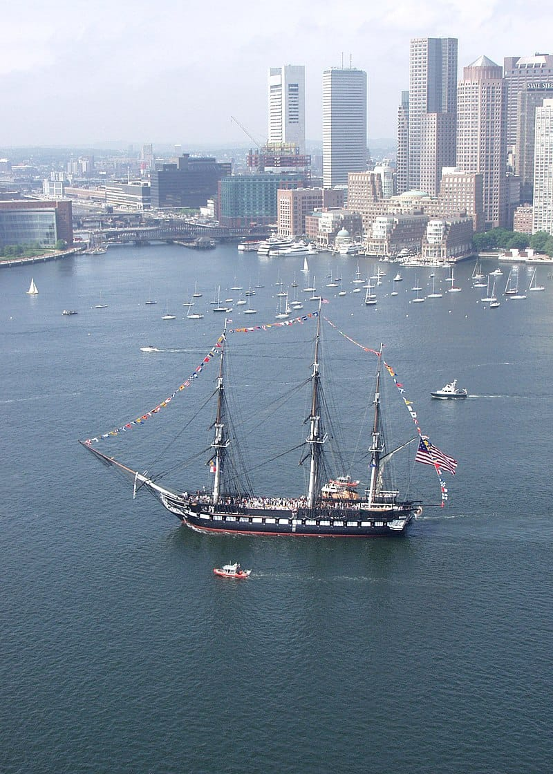 """USS Constitution, the world's oldest commissioned warship afloat, sails past downtown Boston on her """"Salute to the Pacific Northwest"""" cruise, July 16, 2005. (U.S. Navy photo by Journalist 1st Class Matt Chabe)"""