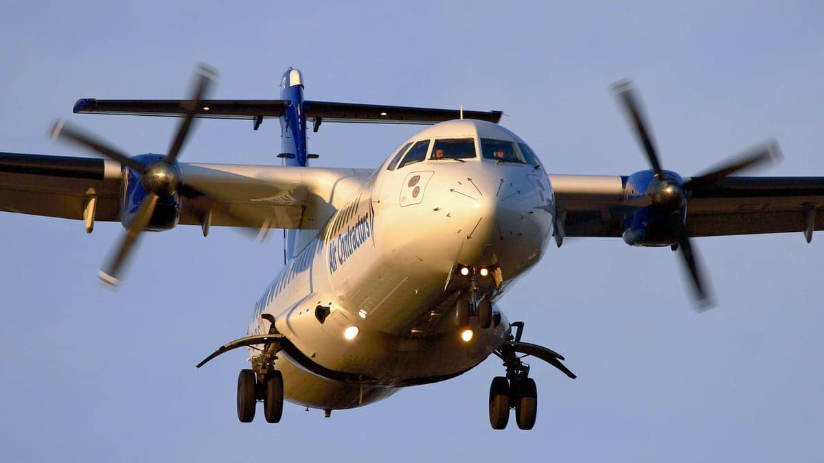 A turboprop ATR plane comes in for landing, view from straight on below the plane.