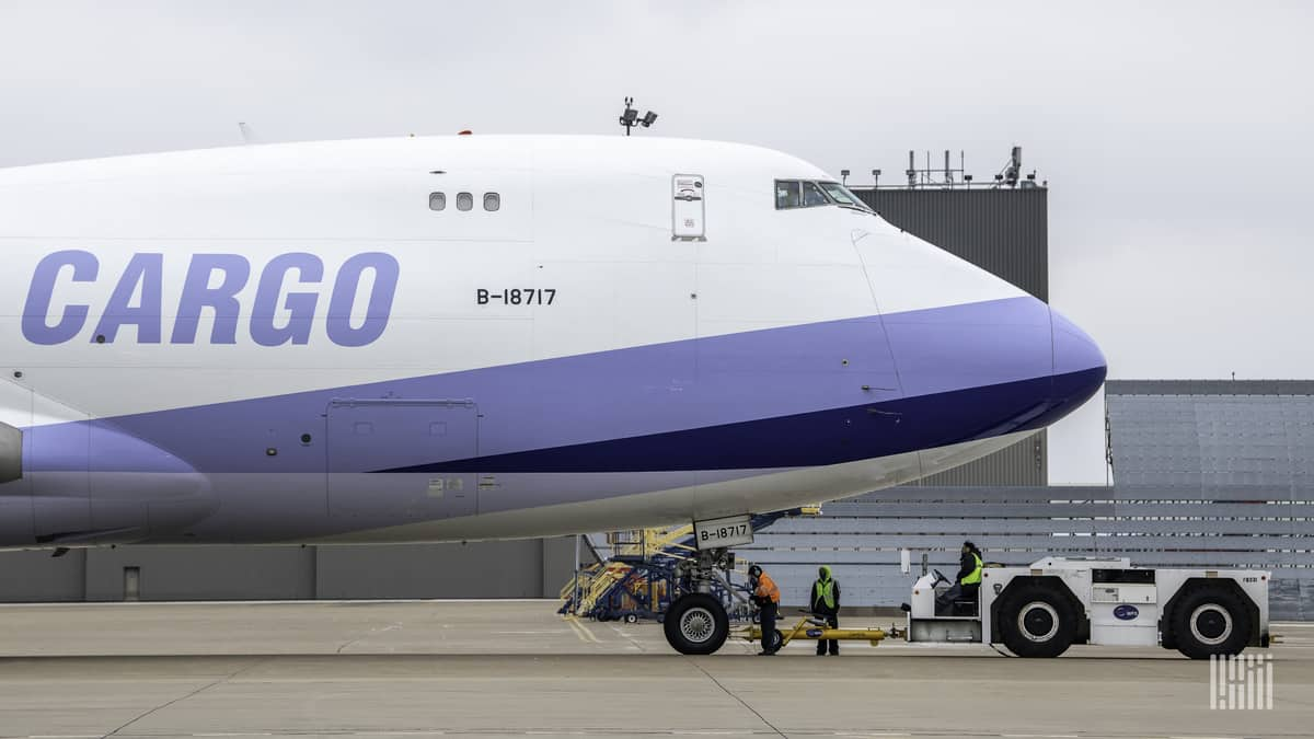 A 747 jumbo jet with white paint and light blue accents with the word CARGO on the side.