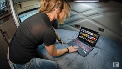 Truck driver looking up movies on her laptop.