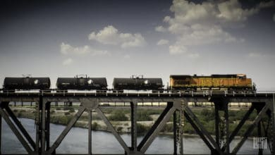 A photograph of a train hauling tank cars over a bridge.