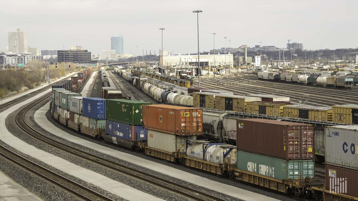 A photograph of a rail yard with parked railcars and intermodal containers.