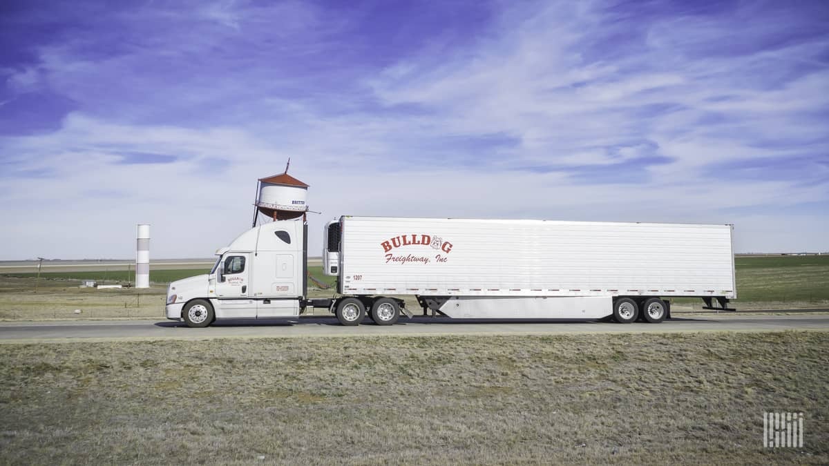A Bulldog Freightway, Inc. tractor and trailer pass a not-so-upright structure. (Photo: Jim Allen/FreightWaves)