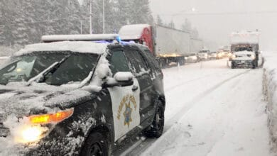 Cars and semis stopped by the CHP on a snowy California highway.