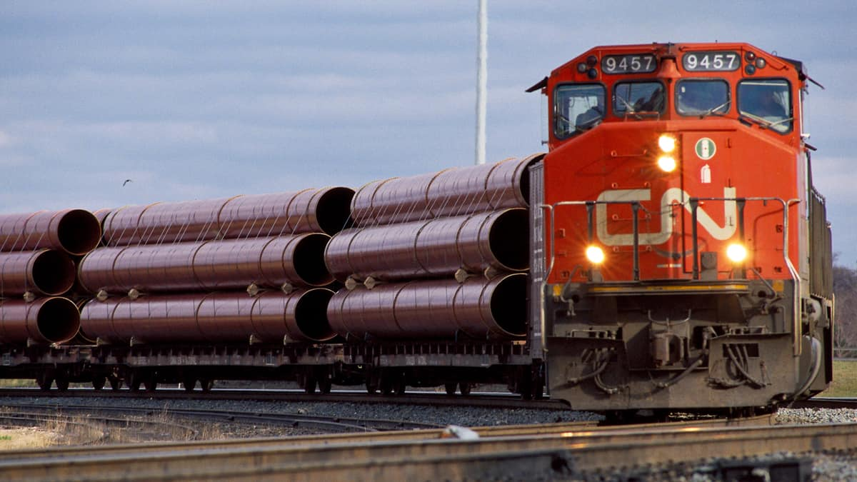 A photograph of a CN train hauling large metal pipes.