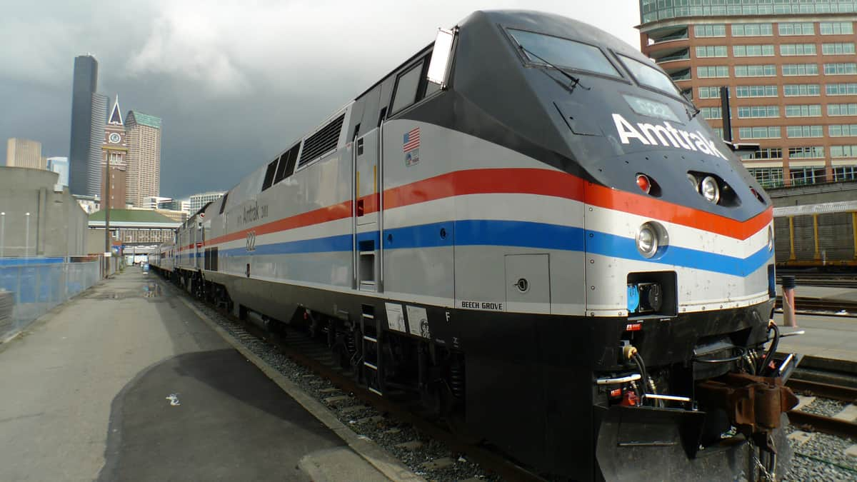 A photograph of an Amtrak train at a city station.